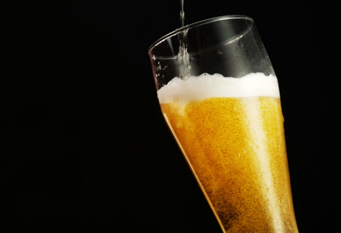 pouring-beer-into-glass-over-black-background-picture-id1015308210